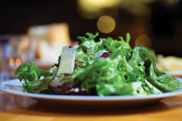 Salad Greens from Angel Valley Farm in  Jonestown, with shaved Parmigiano-Reggiano cheese and a  fresh lemon juice and Extra Virgin  Olive Oil Vinaigrette Dressing